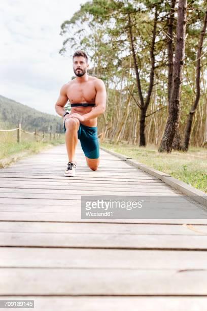 Barechested man exercising on boardwalk