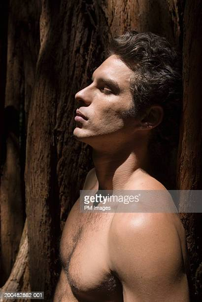 bare-chested man leaning against tree, eyes shut, side view - barechested bare chested ストックフォトと画像