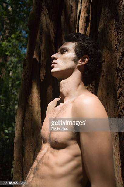 bare-chested man leaning against tree, side view - barechested bare chested ストックフォトと画像