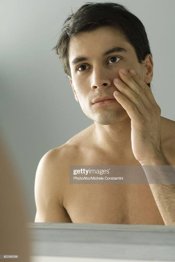 Bare-chested man looking at self in mirror, touching face : Stock Photo
