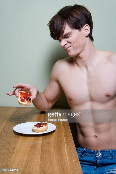 Barechested Man Making Face and Holding Bagel
