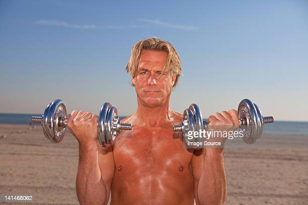 Bare-chested man on beach with weights