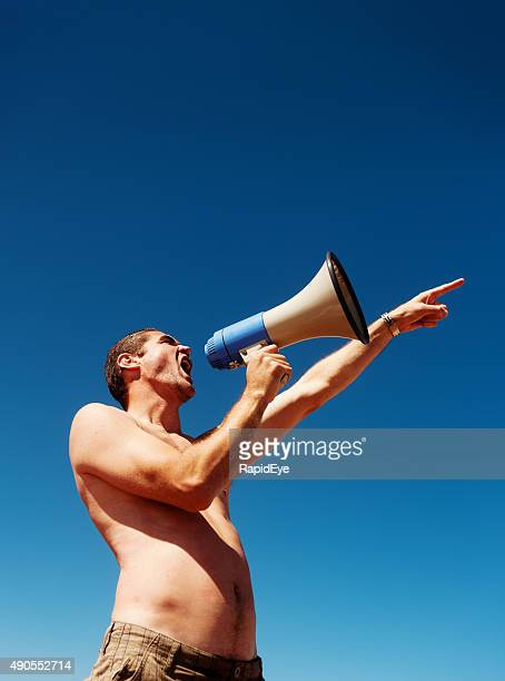 Bare-chested man pointing at something shouts into bullhorn