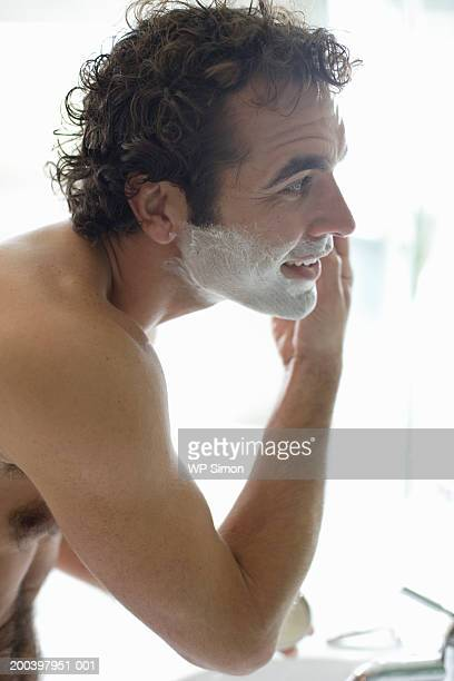 bare-chested man shaving, side view, close-up - barechested bare chested ストックフォトと画像