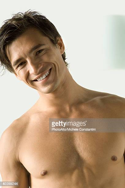 Bare-chested man smiling at camera, head tilted,  portrait