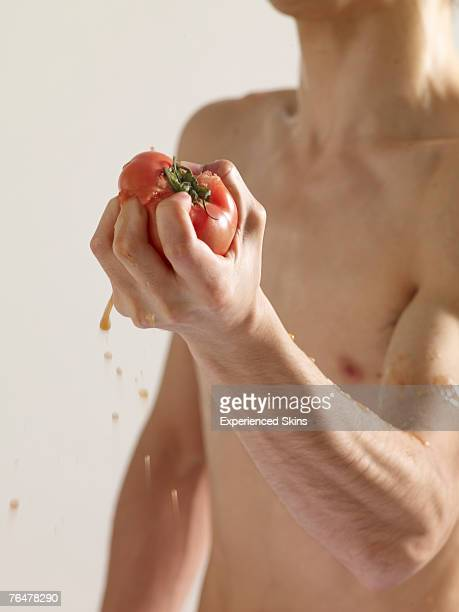 Bare-chested man squeezing a tomato in his hand