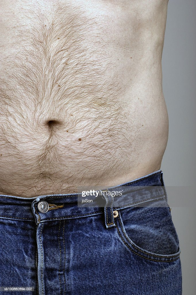 Barechested man standing against grey background, close-up, mid section : Stock Photo