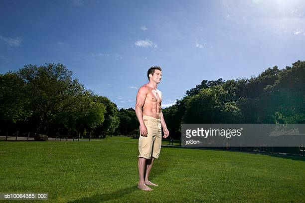 Barechested man standing on grass, smiling