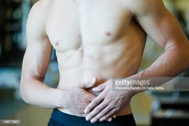 Barechested man with hands on stomach, mid section