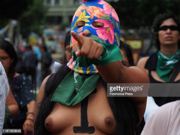 Barechested masked female demonstrators wearing green handkerchiefs performing in a feminist flash mob A Rapist in Your Path in protest of violence...