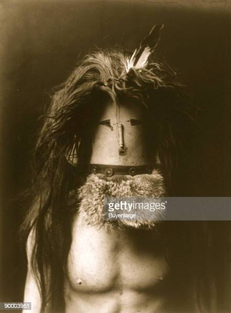 Bare-chested Navajo man wearing mask of Haschebaad, a benevolent female deity.