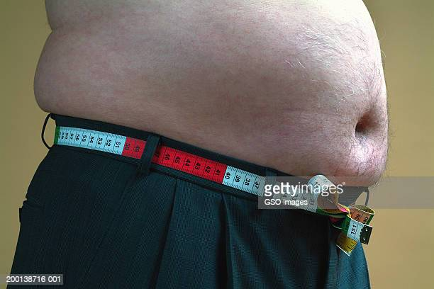 Bare-chested senior man using tape measure as belt, mid section