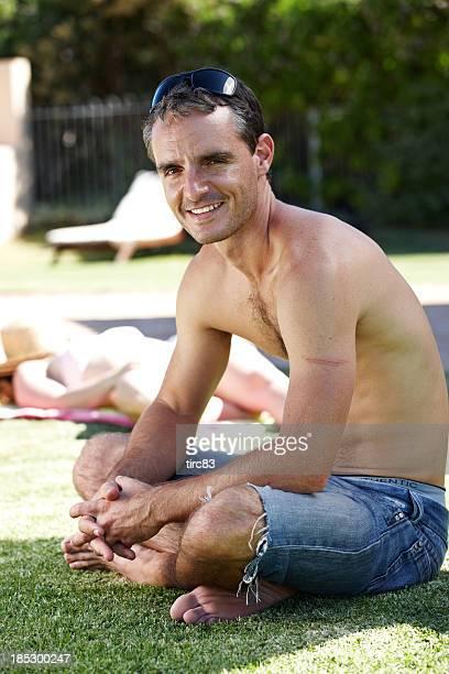bare-chested lächelnd mann auf gras in lotussitz - chest barechested bare chested stock-fotos und bilder