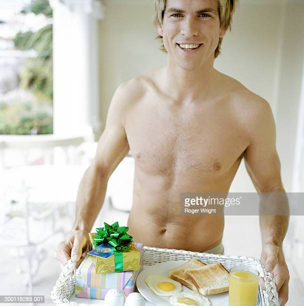 bare-chested young man holding tray with breakfast and gifts, portrait - chest barechested bare chested foto e immagini stock