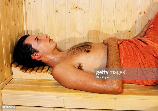 a bare-chested young man lying in a sauna with towel around his waist - bare chested man foto e immagini stock