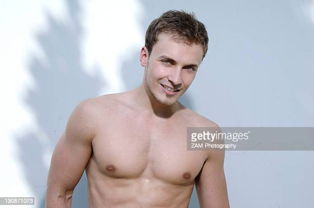 Bare-chested young man smiling, portrait