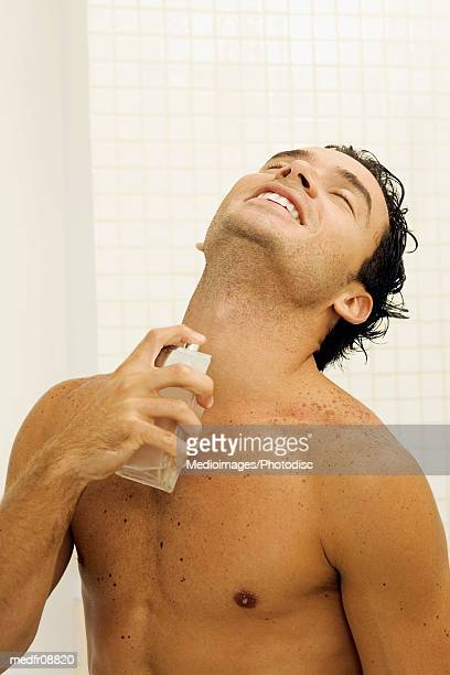 Bare-chested young man spraying cologne on neck in bathroom