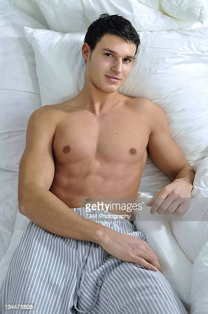 Bare-chested young man wearing pyjama bottoms lying in bed