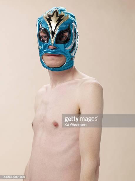 Barechested young man wearing superhero mask