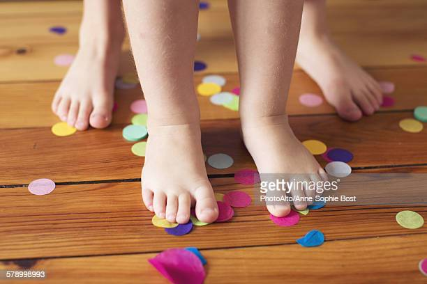 Barefeet and confetti on hardwood floor