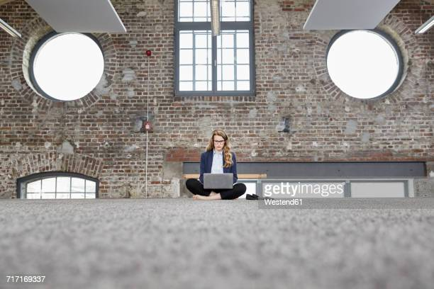 Barefeet businesswoman sitting on the floor in a loft using laptop