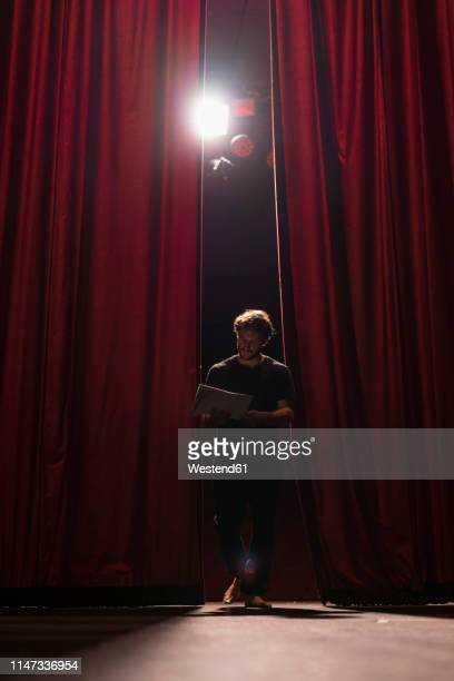 barefoot actor walking on stage of theatre studying script - acteur photos et images de collection