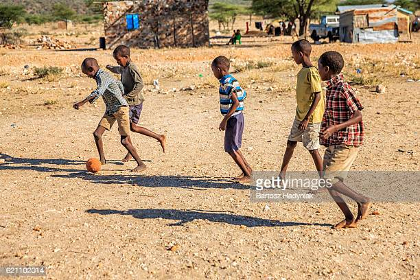 Barefoot African children playing football in the village, East Africa