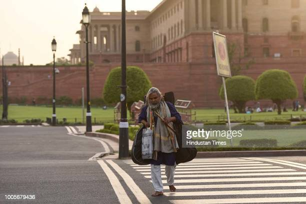 Barefoot and dressed unassumingly Guitar Rao walks with bag full of flutes and a guitar after spending his daily four hour schedule at Vijay Chowk...