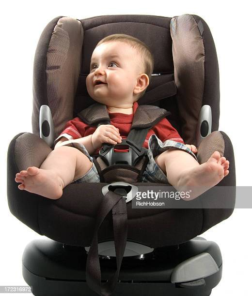 Barefoot baby sitting in car seat