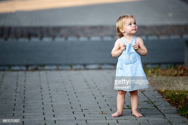 Barefoot blond little girl standing on pavement looking up