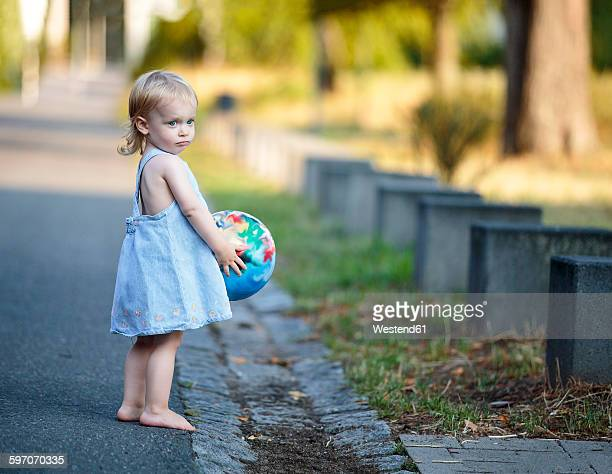 Barefoot blond little girl standing with her ball at roadside