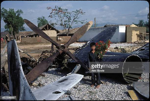 A barefoot boy holding flowers pauses amid the relics of French defeat in the town of Dien Bien Phu before joining celebrations commemorating the...