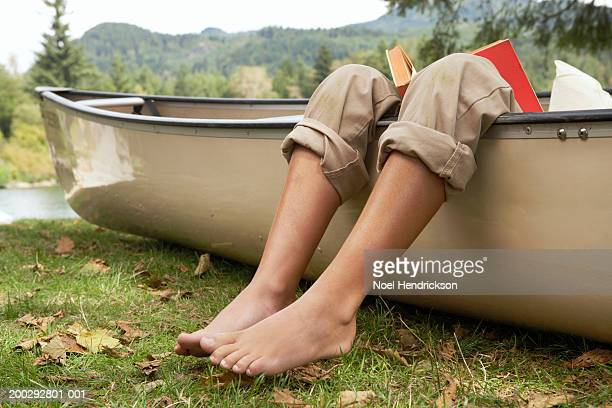 barefoot boy (9-11 years) reading book in canoe by lake, low section, close-up of legs over edge of canoe - rolled up pants stock pictures, royalty-free photos & images