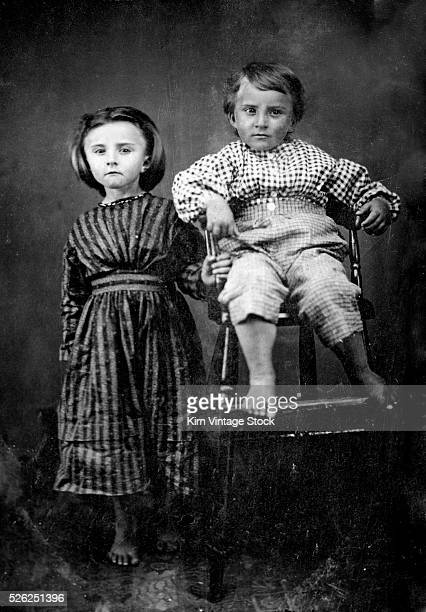 Barefoot brother and sister pose as still as possible for a time exposure 19th century portrait