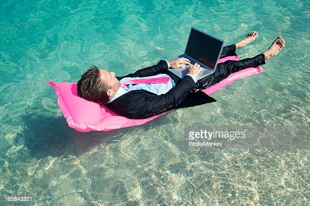 Barefoot Businessman Floating Working at Laptop on Tropical Waters