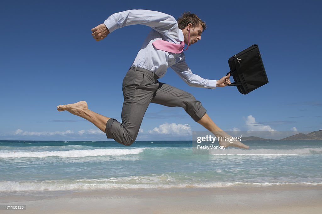 Barefoot Businessman Rushes Past Beach with Briefcase : Stock Photo