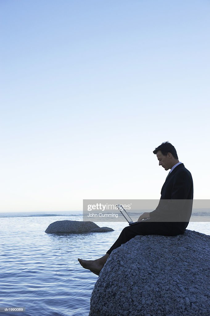 Barefoot Businessman Sitting on a Rock in the Sea and Using a Laptop Computer : Stock Photo