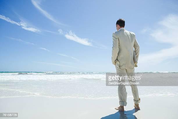Barefoot businessman standing on beach, facing ocean, rear view