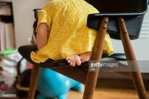 Barefoot Caucasian baby girl laying on chair
