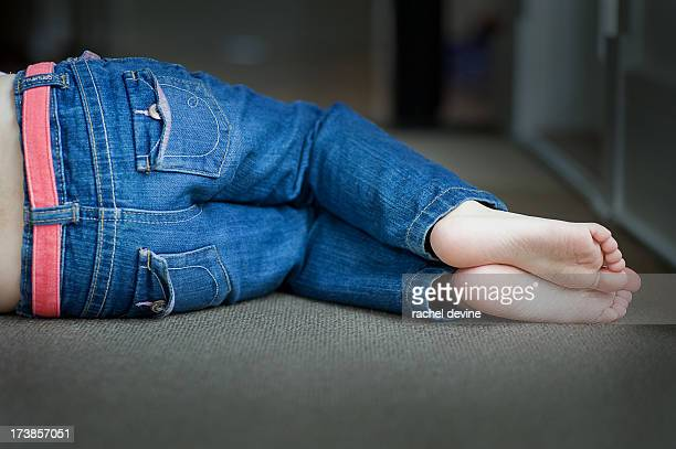 barefoot child napping on floor in jeans - girls barefoot in jeans stock photos and pictures