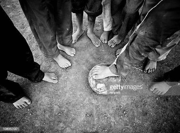 Pieds nus enfants debout autour d'un ballon de football