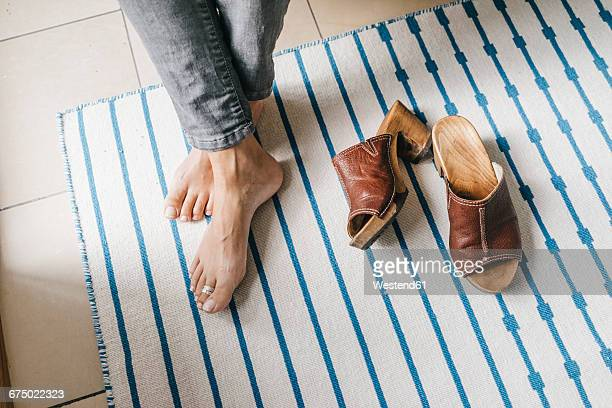 Barefoot feet of a woman beside her shoes