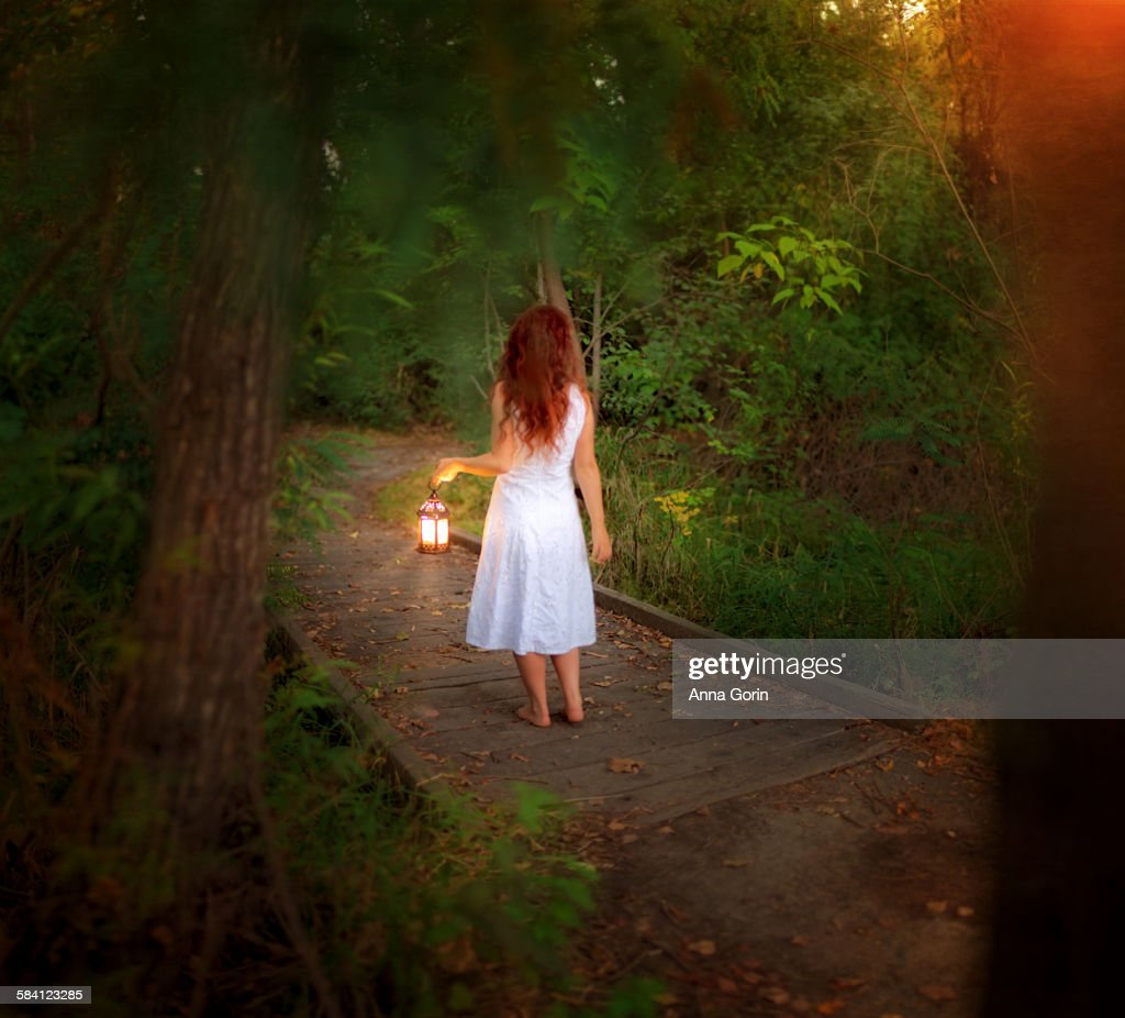 Barefoot girl in forest with lantern, rear view : Stock Photo