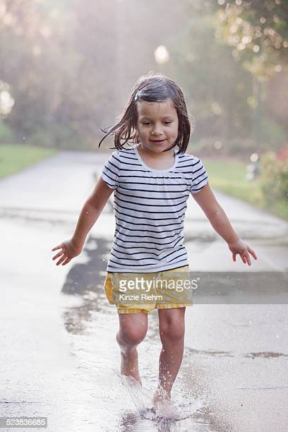 barefoot girl running through puddles on rainy street - wet t shirt girls stock photos and pictures