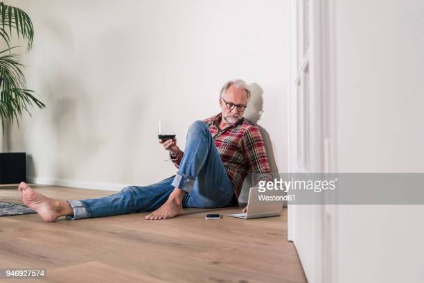 barefoot man sitting on the floor at home relaxing with laptop and glass of red wine - checked shirt stock photos and pictures
