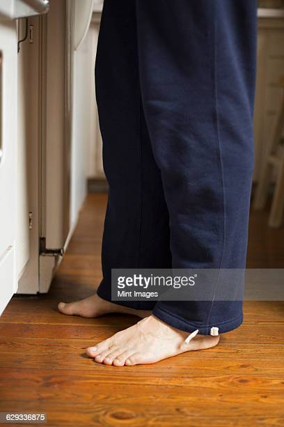 barefoot man standing in a kitchen. - tracksuit bottoms stock pictures, royalty-free photos & images