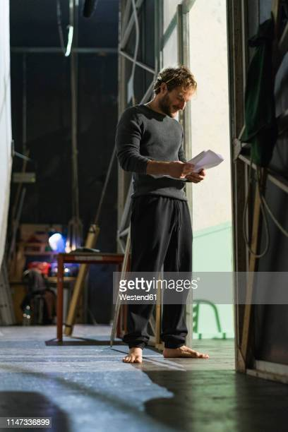 barefoot man standing in theatre stage reading script - ator - fotografias e filmes do acervo