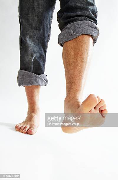 Barefoot man wearing rolled up jeans stepping forward low section