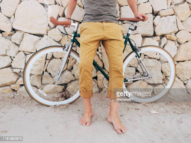barefoot man with fixie bike in front of natural stone wall on the beach, partial view - rolled up trousers stock pictures, royalty-free photos & images