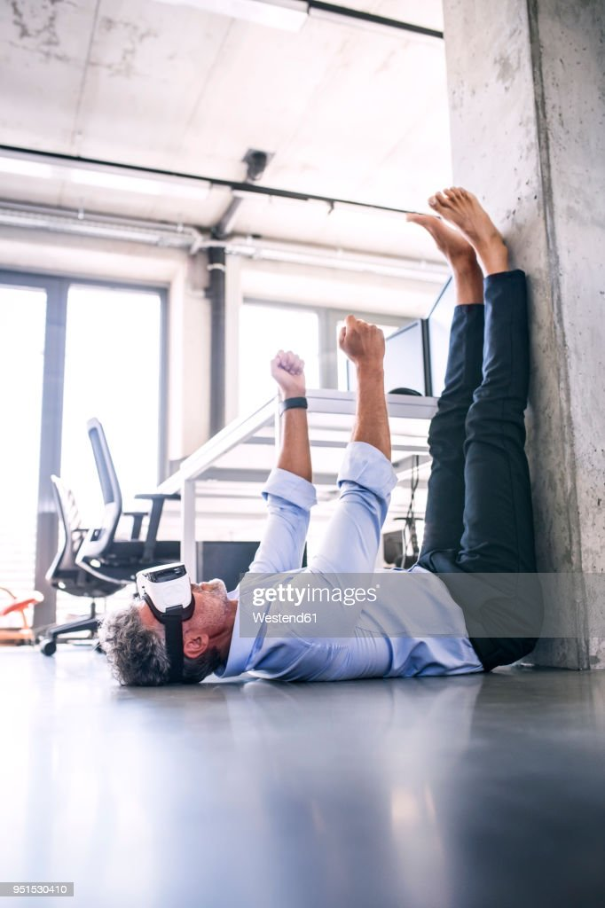 Barefoot mature businessman lying on floor in office wearing VR glasses : Stock-Foto